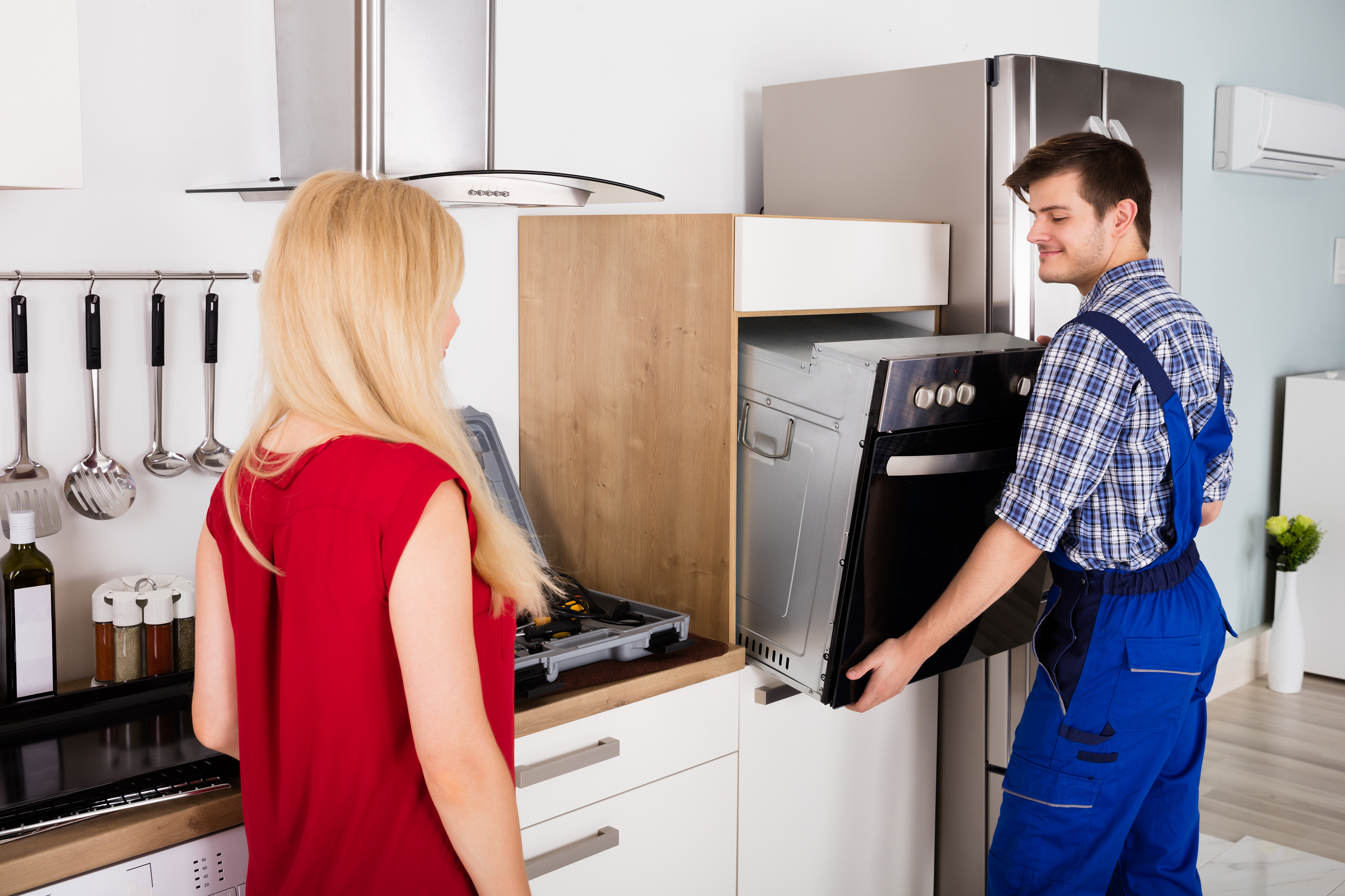 Male Worker Installing Oven For Repairing While Young Woman Standing In Kitchen